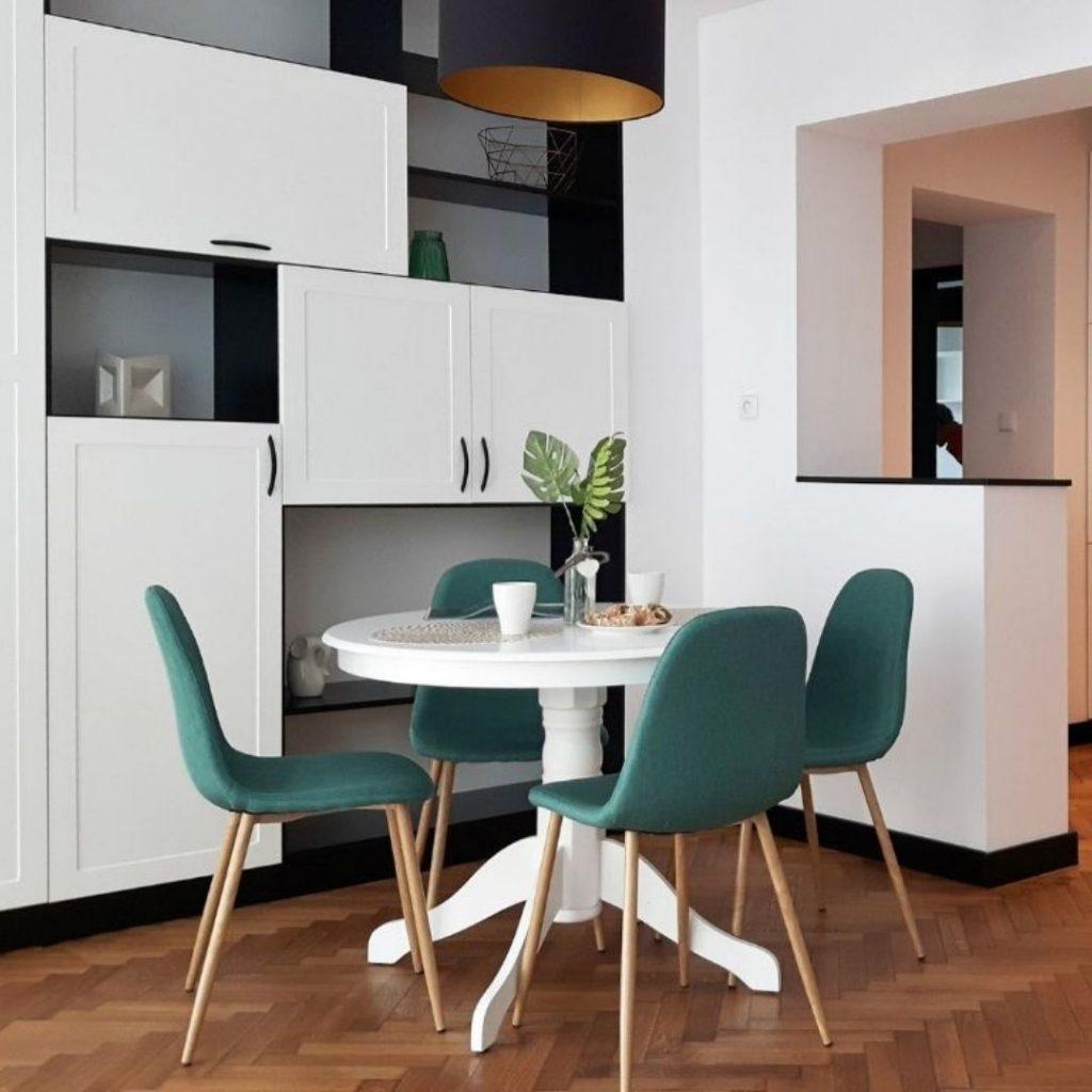 Salon z aneksem, biały okrągły stół, zielone krzesła z drewnianymi nogami