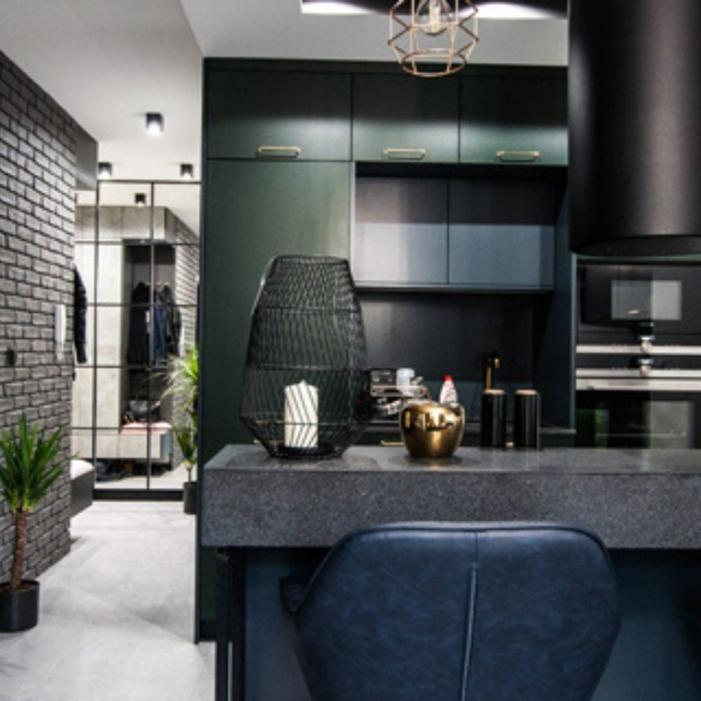Kuchnia z ciemno zielonymi frontami , industrialne lustro, złote dodatki