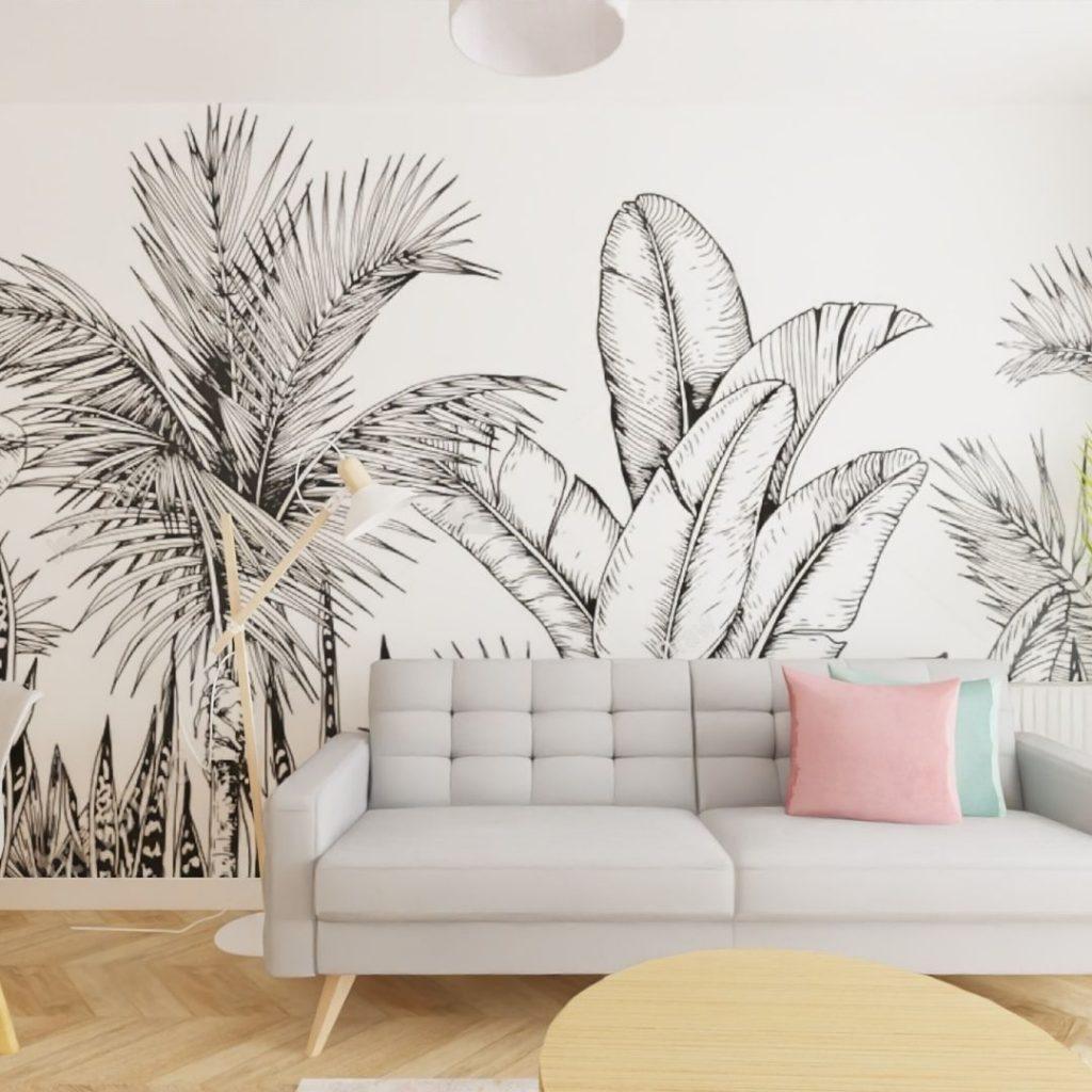 szara sofa, różwe poduszki, malowana grafika na ścianie
